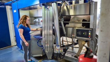 student from Aeres University of Applied Sciences with DeLaval milking robot at dairy farm at Aeres Farms